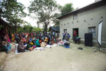 Community people watch an enter-education drama video to learn about process and services of village courts for resolving their petty disputes.